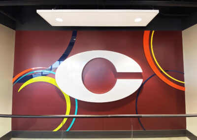 White acrylic letter C on a dark red wall with other acrylic graphic elements