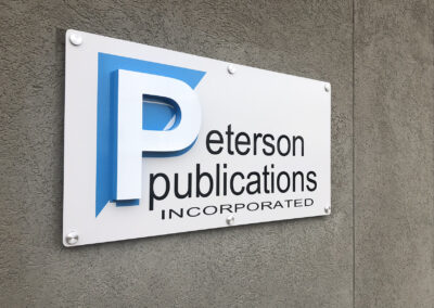Acrylic dimensional P on a standout sign that says Peterson Publications