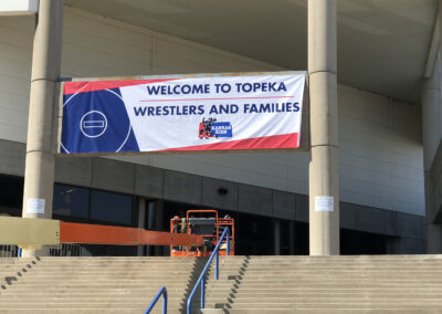 Installation of a banner welcoming wrestlers to Topeka Kansas