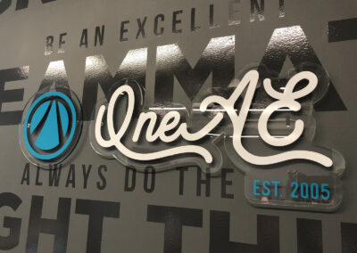 Contour cut acrylic sign that says One AE over a brand wall