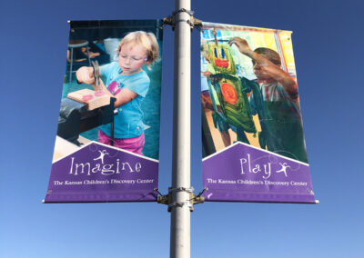 Two pole banners featuring images of children with the words imagine and play below