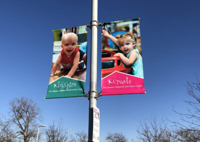 two pole banners featuring images of children with the words inspire and create below